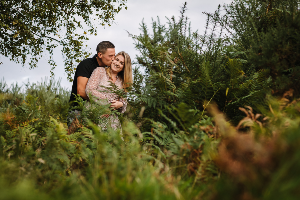 happy natural authentic image couple embrace in ferns headily heath surrey hills unposed engagement session outdoor pre-wedding_shoot natural light documentary wedding photographer