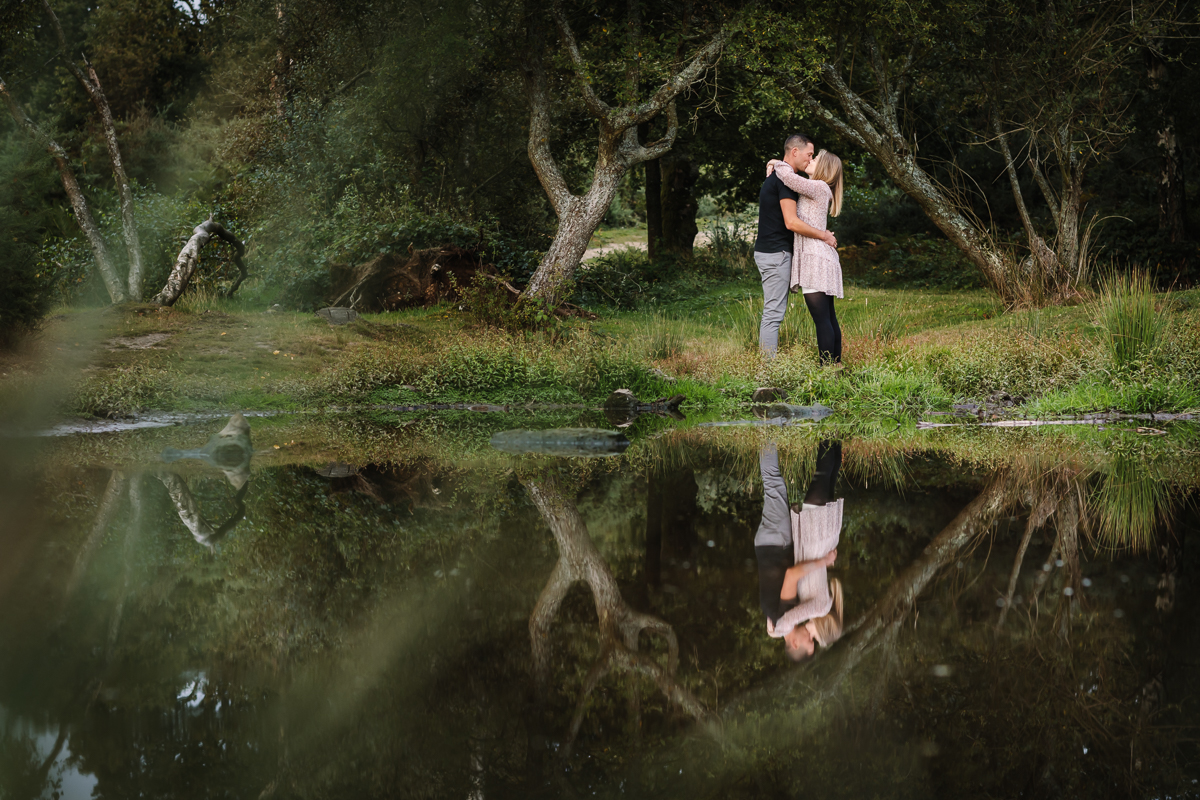 natural authentic image couple embrace reflection in water pond headily heath surrey hills unposed engagement session outdoor pre-wedding_shoot natural light documentary wedding photographer