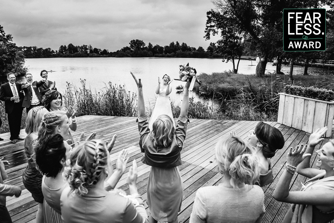 fearless wedding photography award bouquet toss black_white bridesmaid catch bridesmaids catching happiness laughter arms up in air cheer