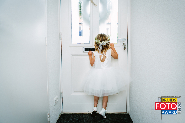bruidsfoto award wedding photography flower girl peeking through front door glass