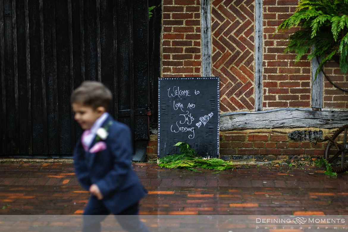 page boy running around outside gildings barn newdigate rustic countryside farm authentic romantic wedding venue venues surrey