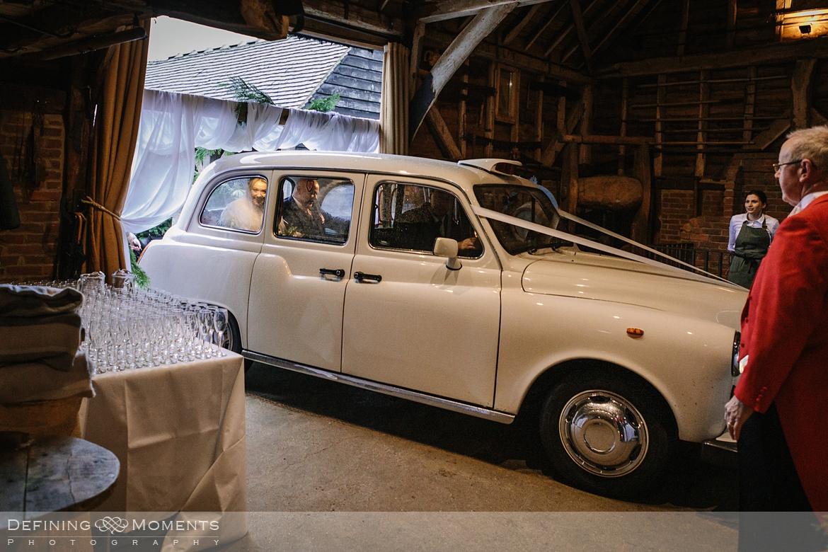 bride arrives in stylish vintage car for ceremony at gildings barn newdigate rustic countryside farm authentic romantic wedding venue