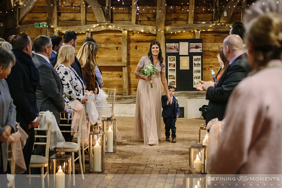 bridesmaids make their entrance for the wedding ceremony in the main barn at gildings barns newdigate rustic countryside farm authentic romantic wedding venue surrey