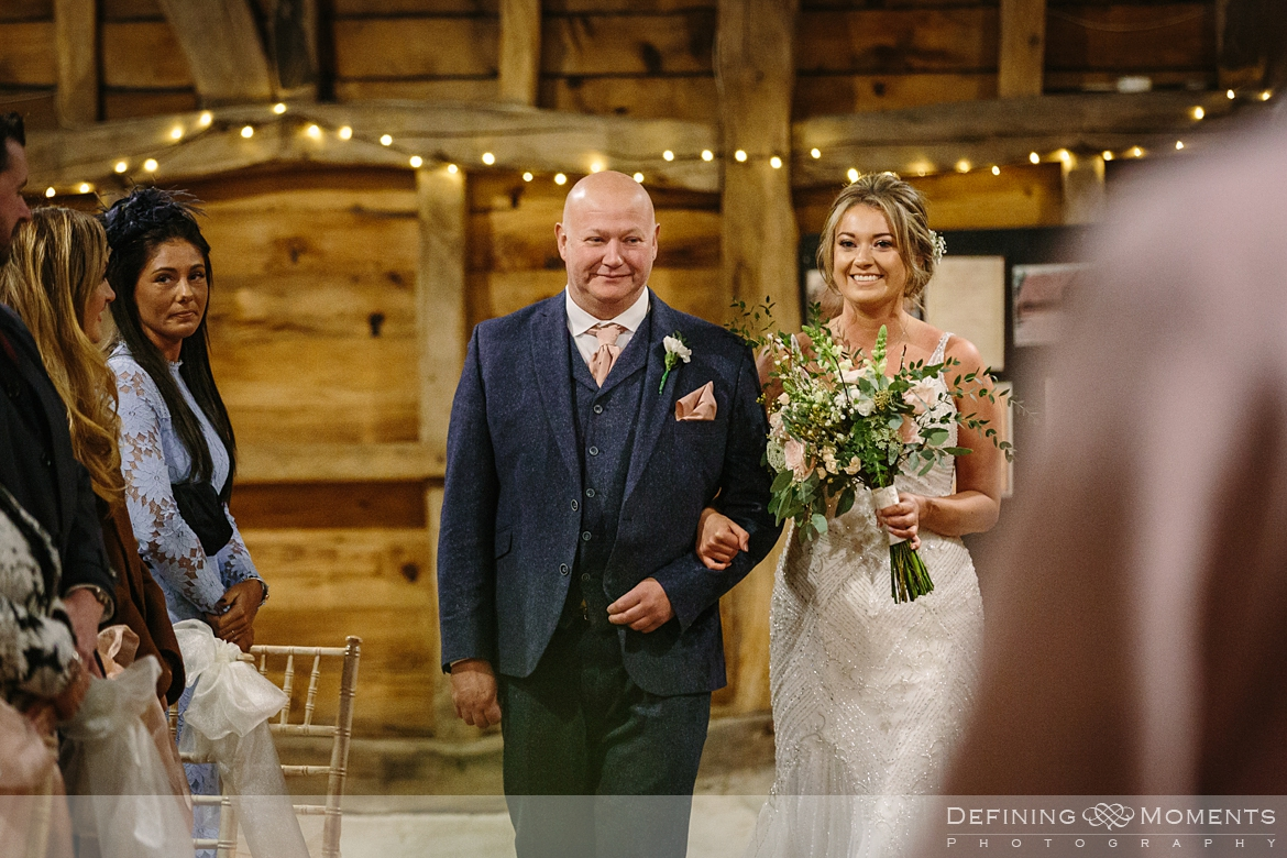 bride and her dad make their entrance for the wedding ceremony in the main barn at gildings barns newdigate rustic countryside farm authentic romantic wedding venue surrey
