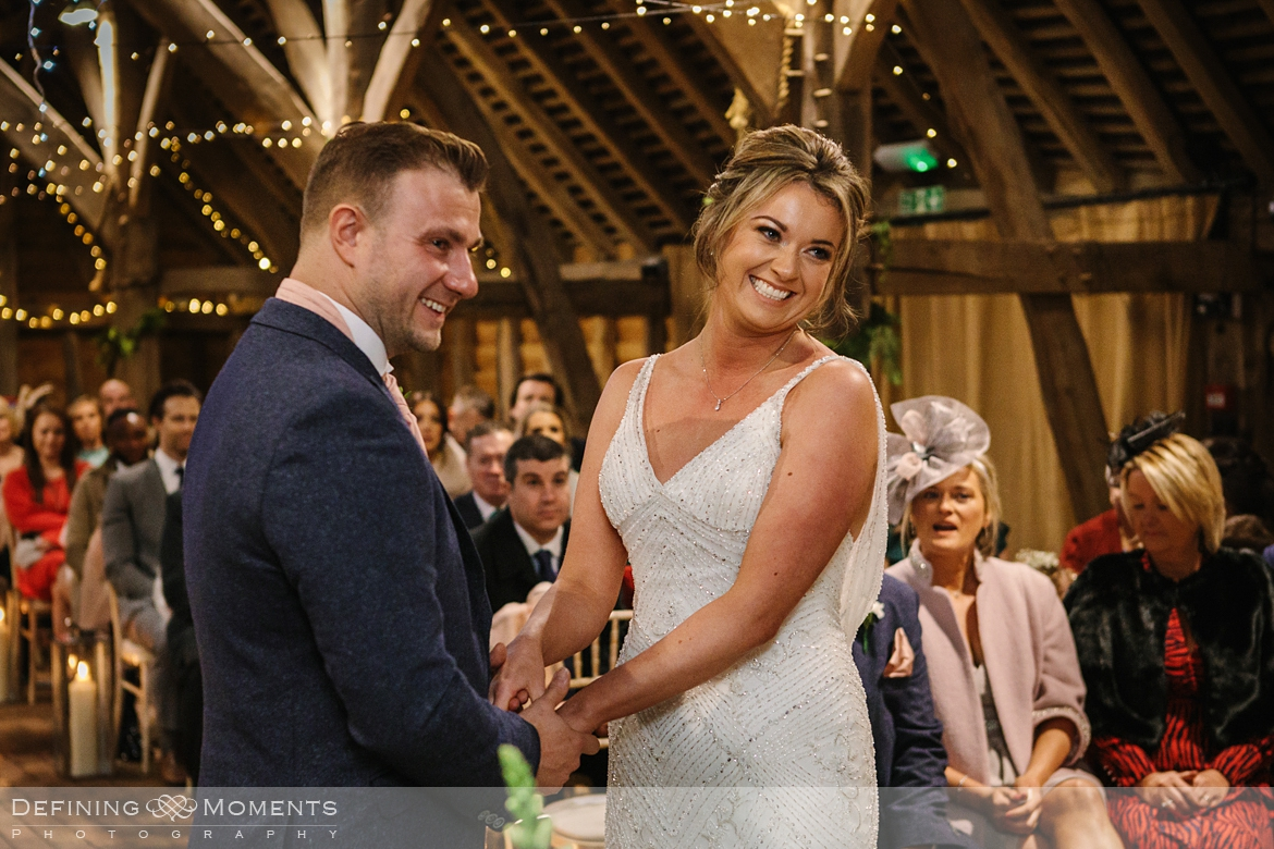 documentary wedding photography of civil wedding ceremony in the main barn at gildings barns in newdigate, a rustic countryside authentic romantic wedding venue in surrey with fairy lights