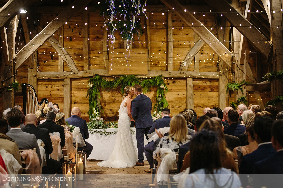documentary wedding photography of wedding kiss during civil wedding ceremony in the main barn at gildings barns in newdigate, a rustic countryside authentic romantic wedding venue in surrey
