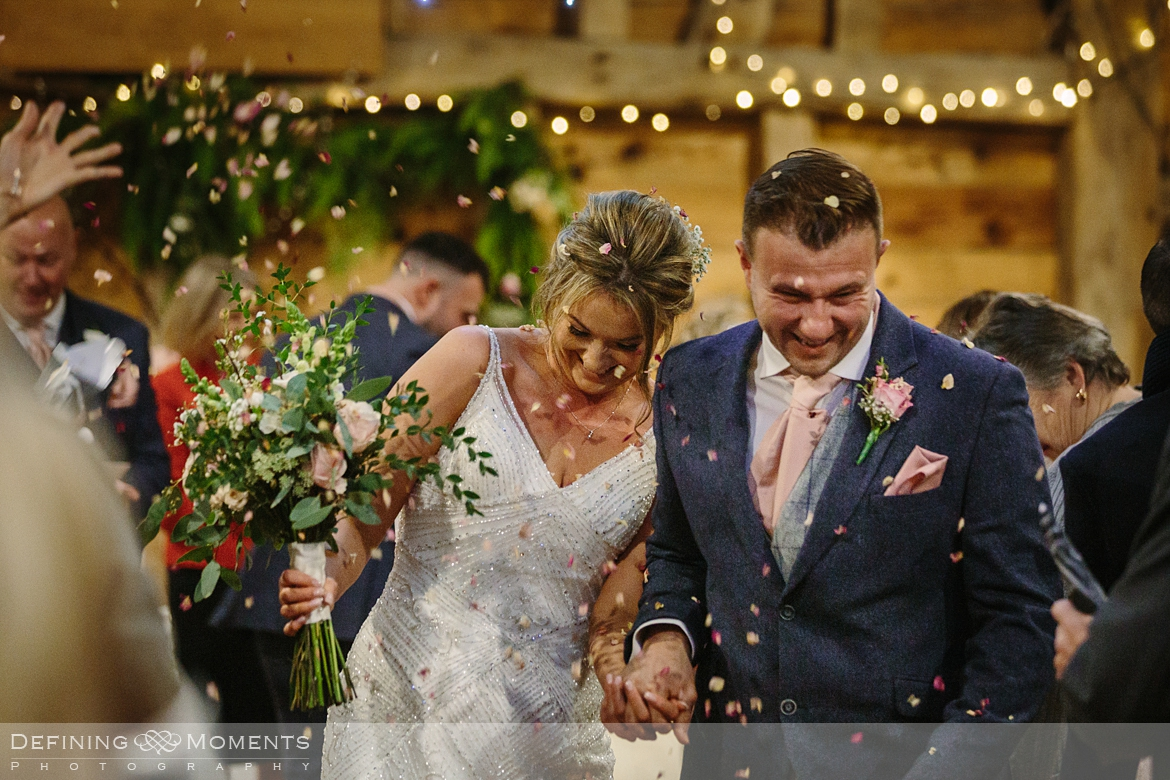 documentary wedding photography of bride and groom just after their civil wedding ceremony in the main barn at gildings barns in newdigate, a rustic countryside wedding venue in surrey with fairy lights