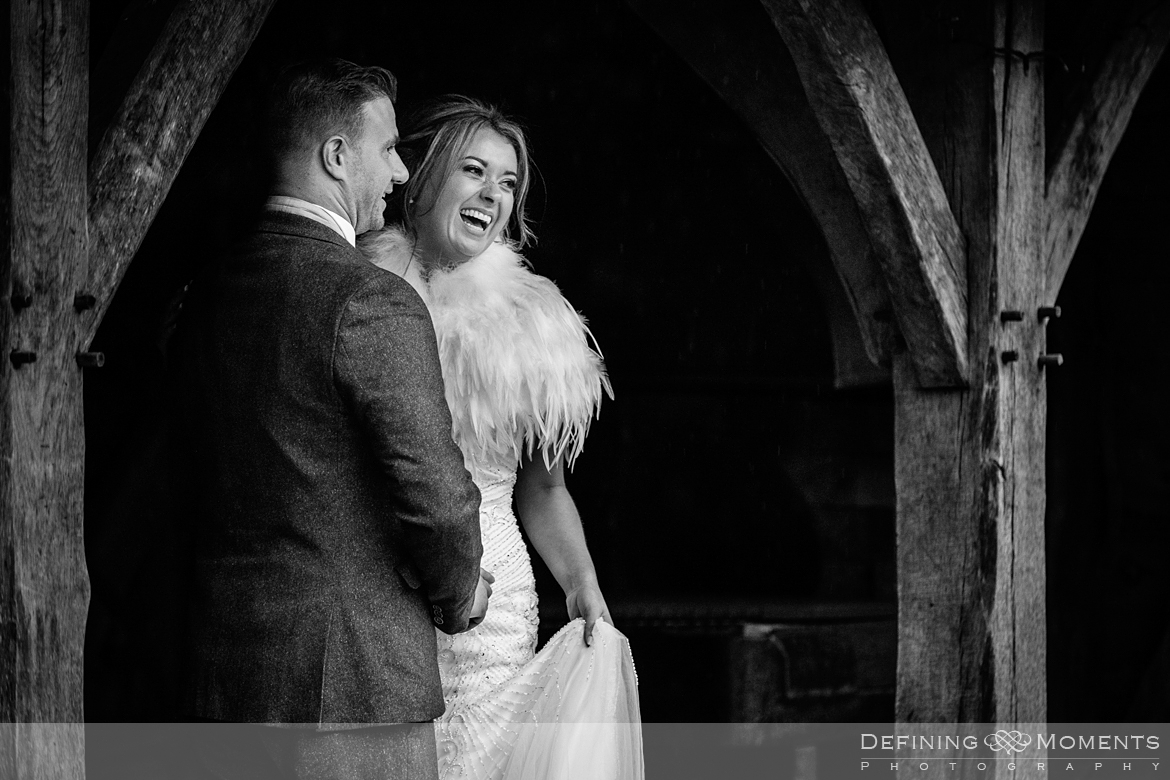 wedding photography couple portraits in courtyard under hovel at gildings barns in newdigate a barn wedding venue near dorking by documentary wedding photographer surrey
