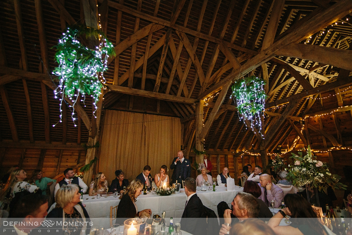 documentary wedding photography of wedding breakfast and speeches in the main barn at gildings barns in newdigate, a rustic countryside wedding venue in surrey with fairy lights