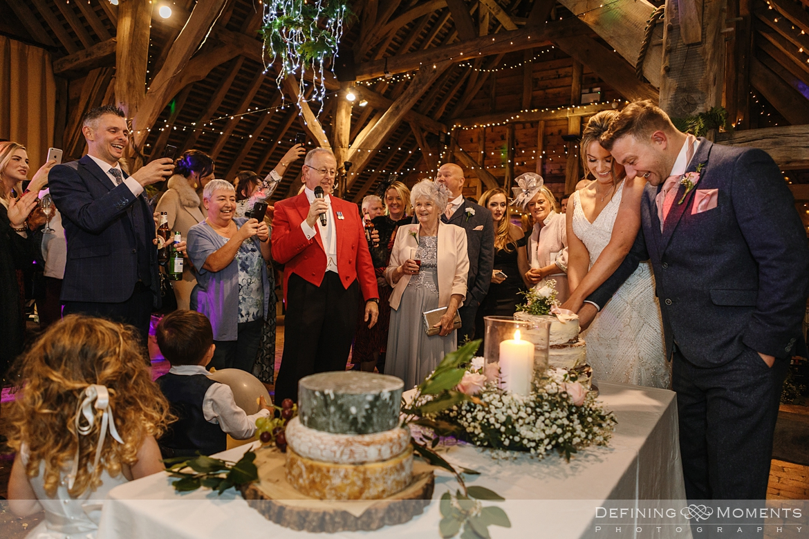 documentary wedding photography of cuttinf of the cake in the main barn at gildings barns in newdigate, a rustic countryside wedding venue in surrey with fairy lights