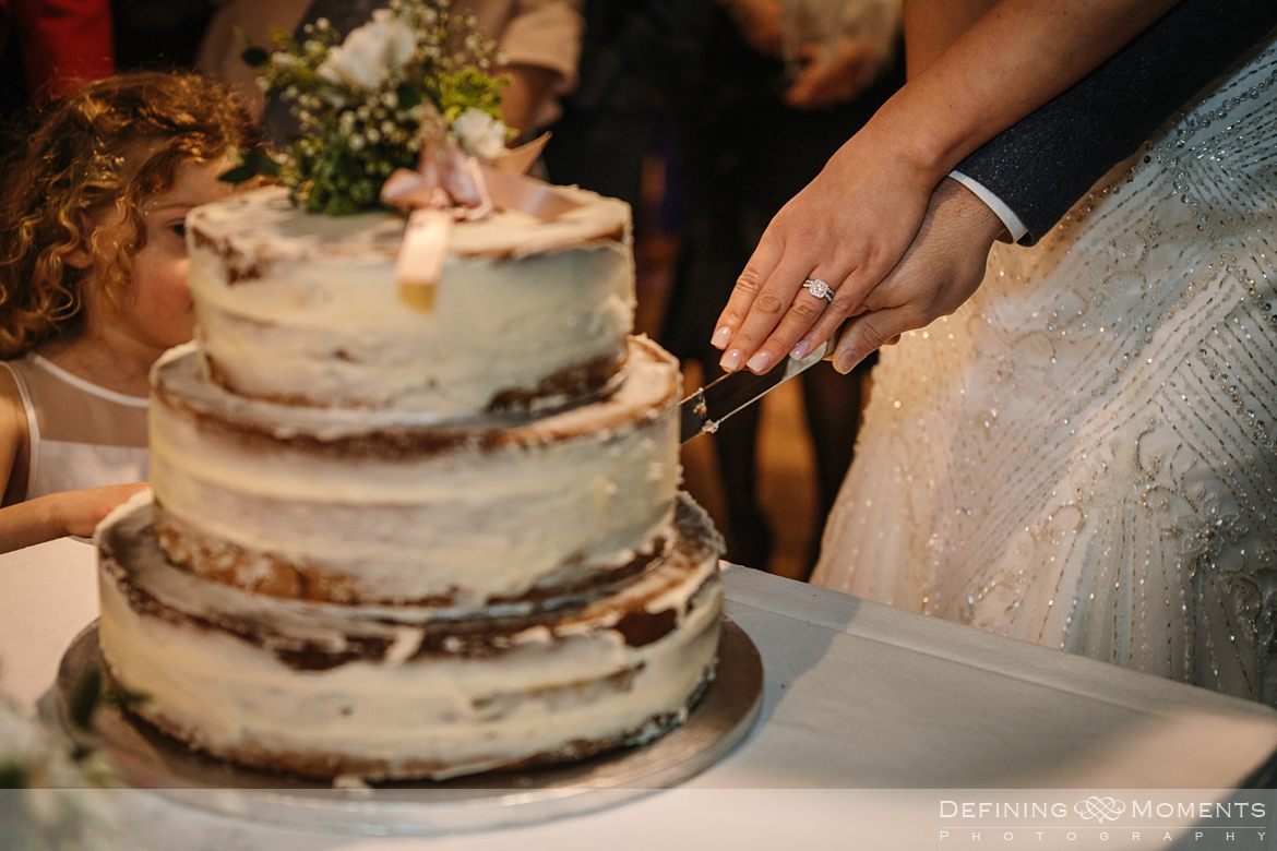 close-up documentary wedding photography of cuttinf of the cake in the main barn at gildings barns in newdigate, a rustic countryside wedding venue in surrey with fairy lights