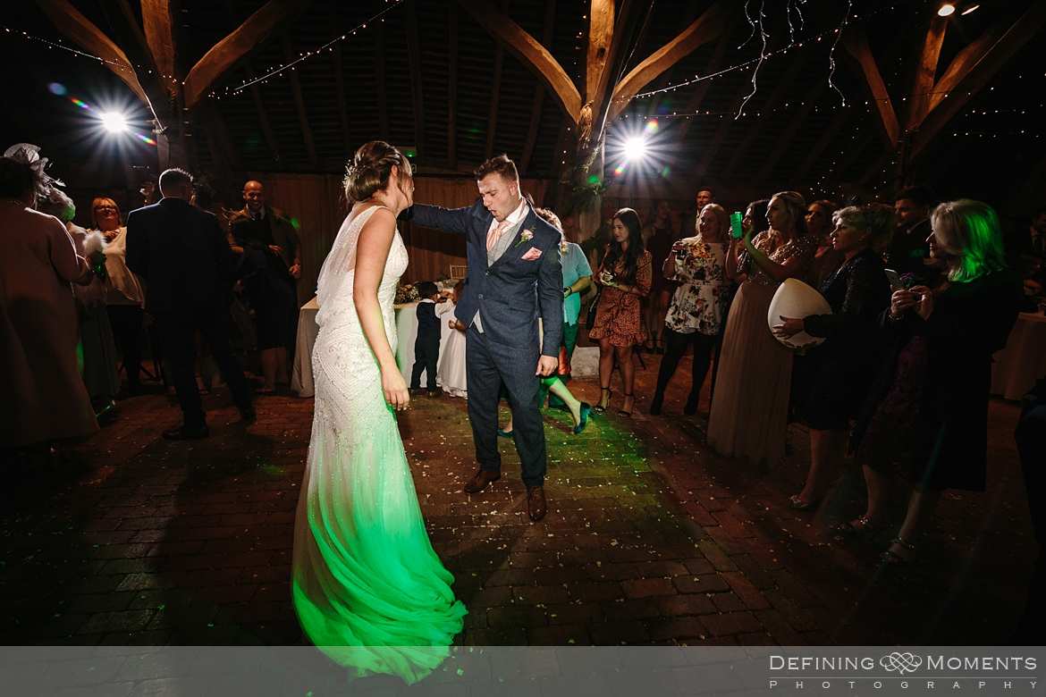documentary wedding photography of bride and groom first dance in the main barn at gildings barns in newdigate, a barn wedding venue in surrey with fairy lights