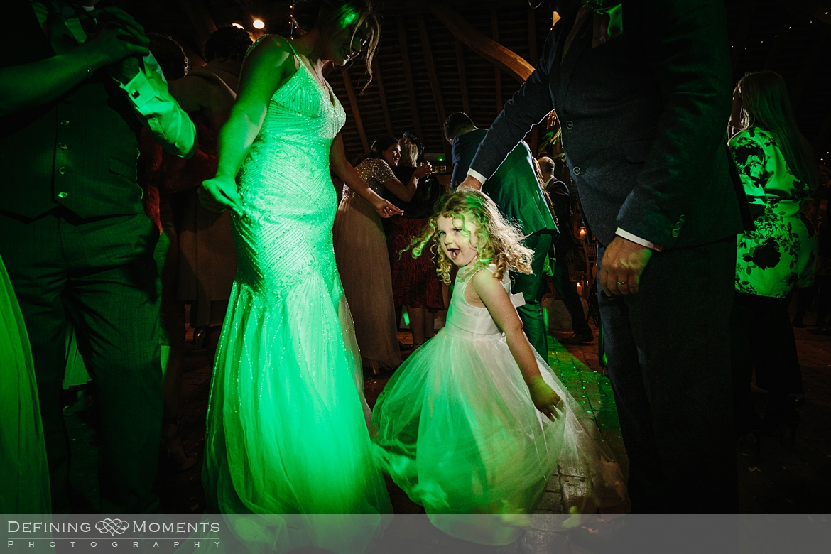flower girl on the dance floor documentary wedding photography of wedding party on the dance floor in the main barn at gildings barns in newdigate, a rustic countryside wedding venue in surrey with fairy lights