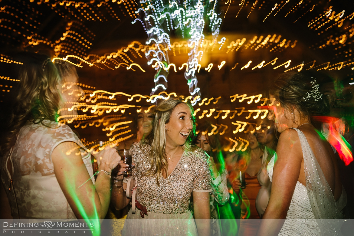 documentary wedding photography of wedding party on the dance floor in the main barn at gildings barns in newdigate, a rustic countryside wedding venue in surrey with fairy lights