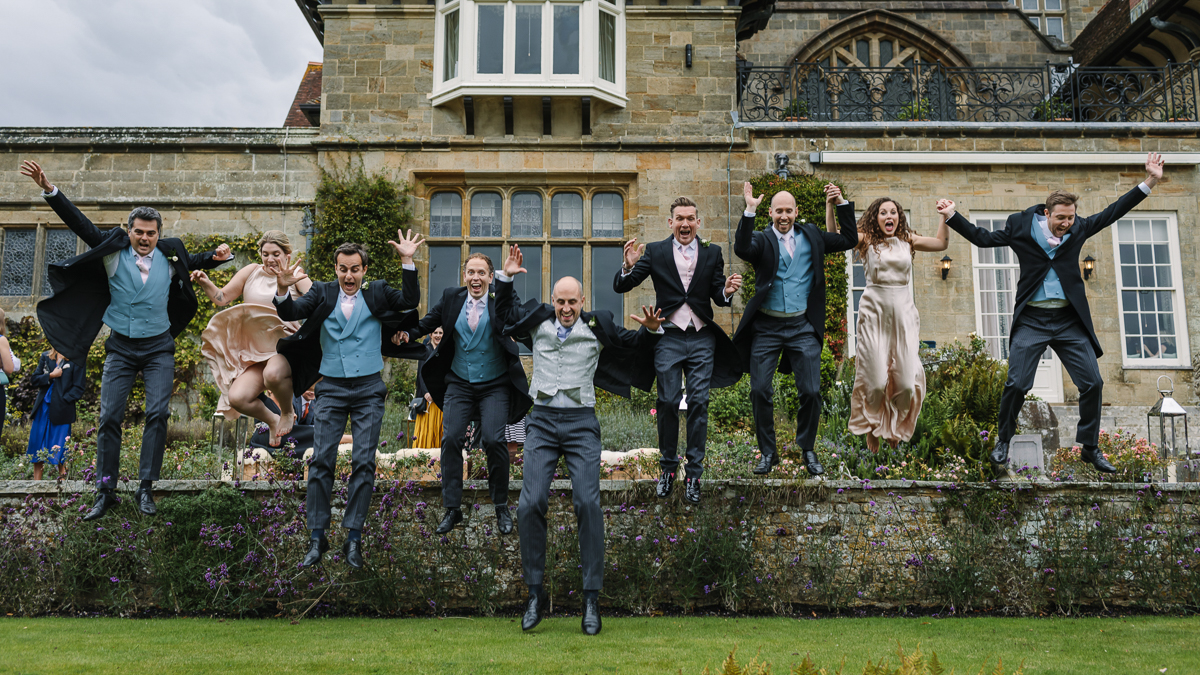 bridal party jump cowdray_house outside terrace wedding reception The_London_Essentials performance performing bride groom country house venue west_sussex award_winning photographer