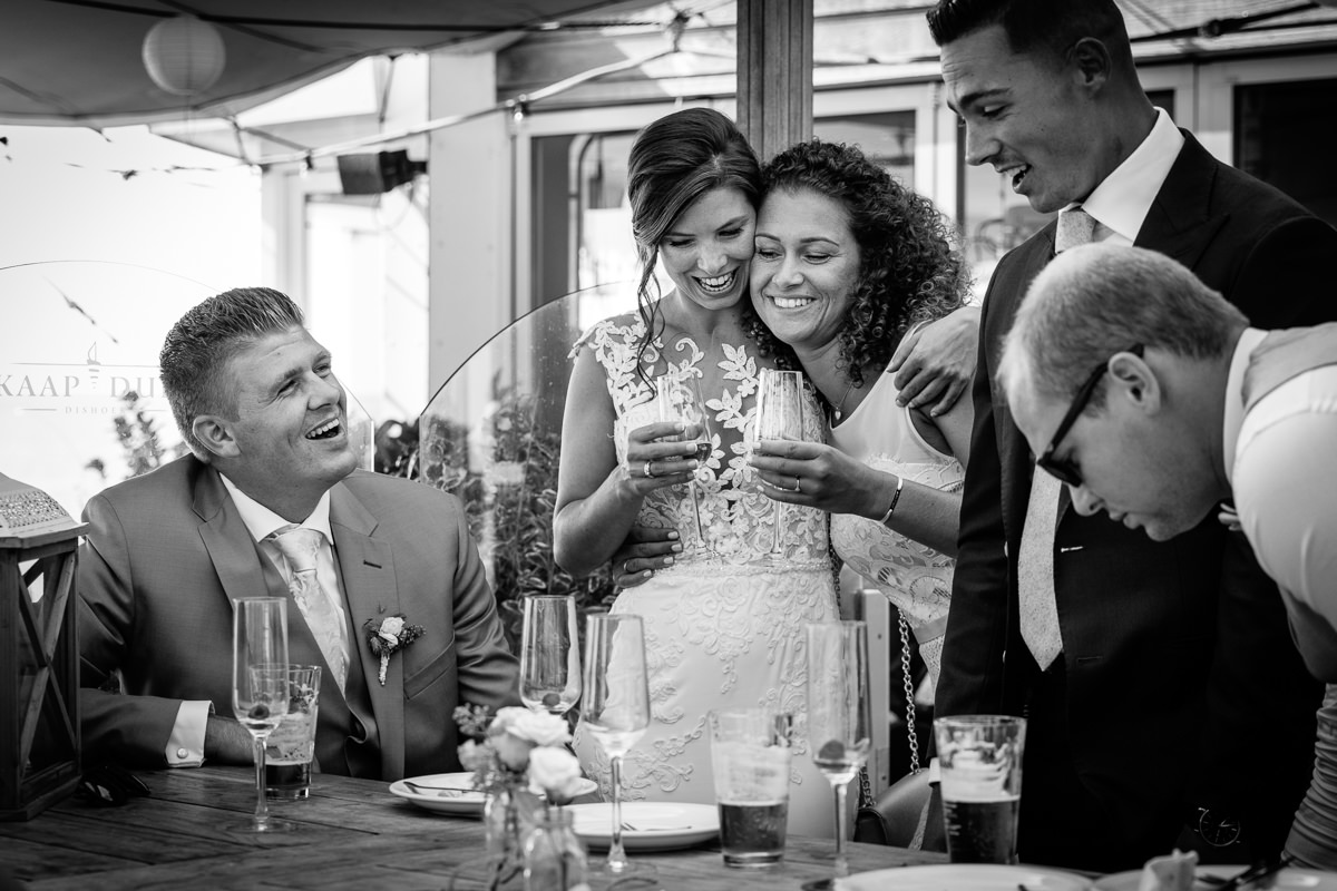 wedding party bride smiling embracing maid_of_honour cuddle smile embrace black_white wedding photo journalistic documentary reportage photographer photo surrey