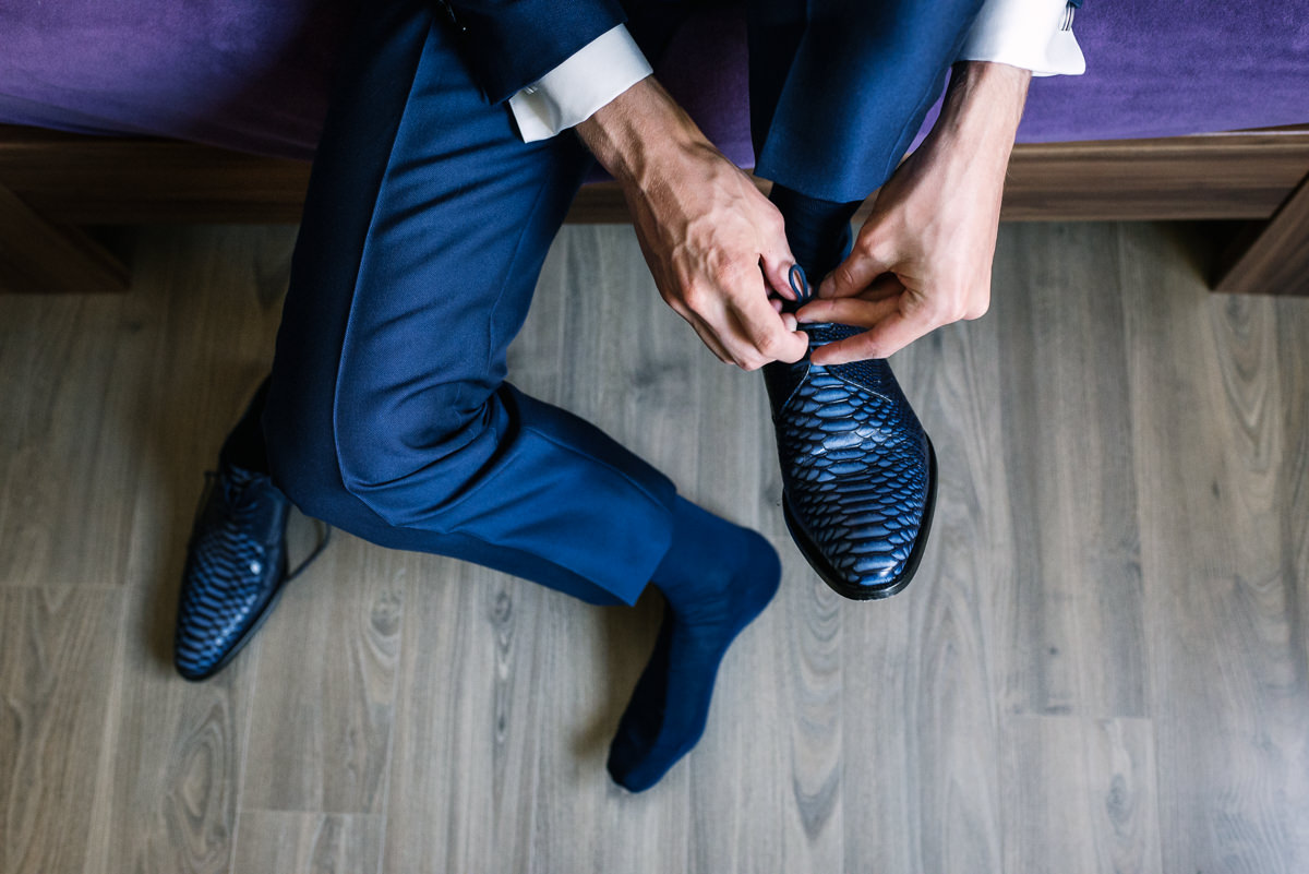 top view wedding shoes groom blue suit donning laces shoelace journalistic documentary reportage photographer photo surrey