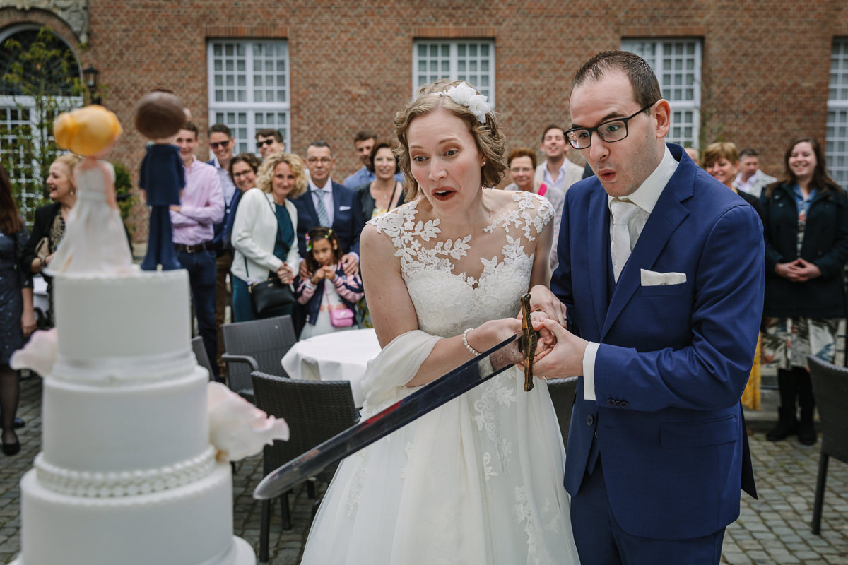 bride groom cutting cake with sword photo journalistic documentary reportage photographer photo surrey