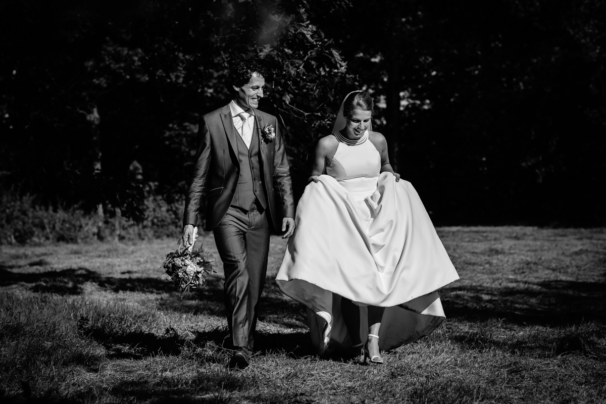 bride groom wedding portrait walking grass black_white wedding photo journalistic documentary reportage photographer photo surrey
