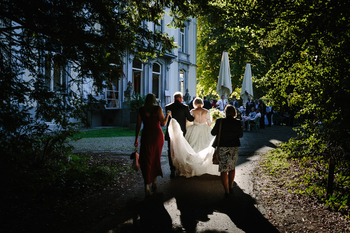 bride groom walking towards venue in sunlightwedding photo journalistic documentary reportage photographer photo surrey