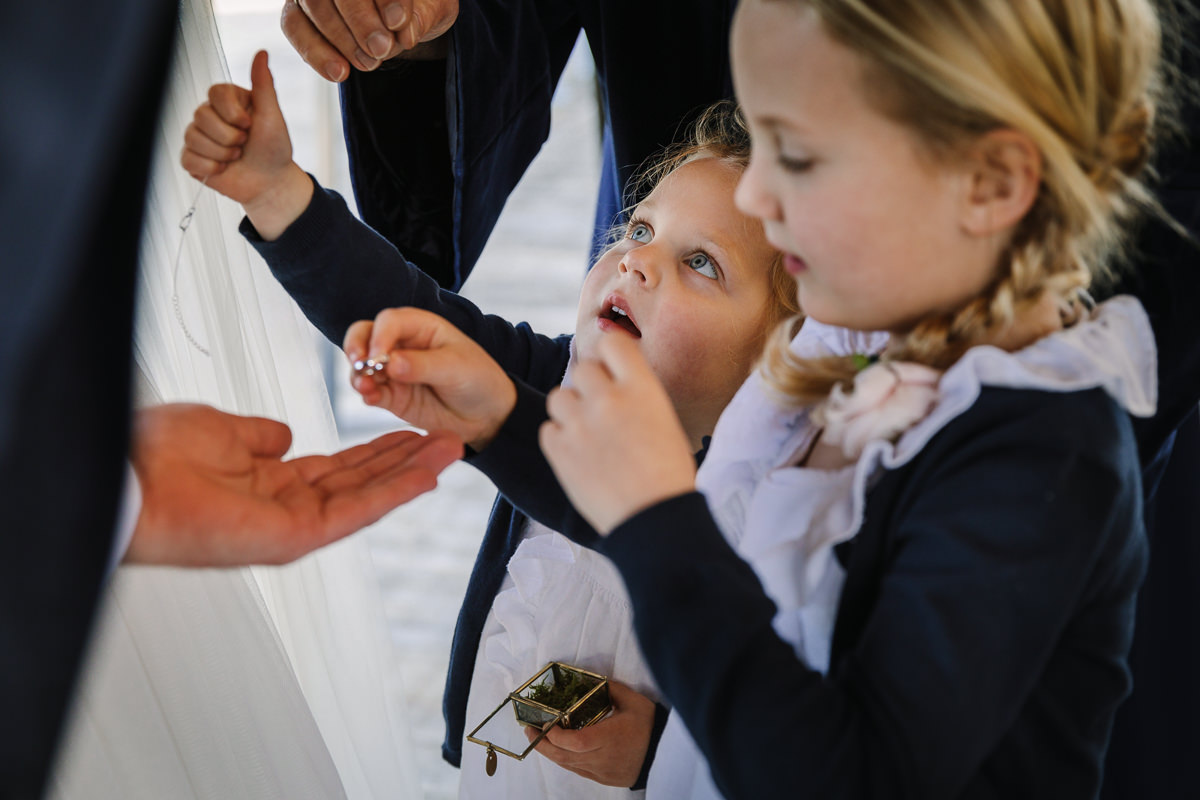 flower girls passing the wedding rings during ceremony