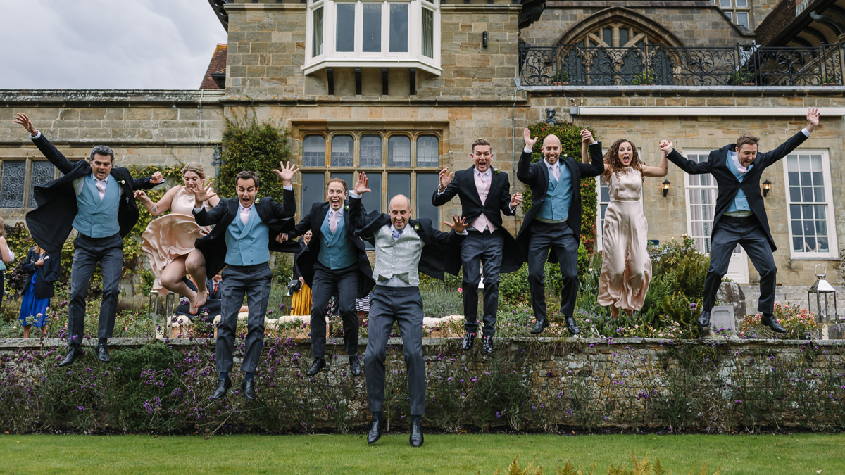 best men groom bridesmaids bride jumping for portrait at cowdray house wedding venue wedding photo journalistic documentary reportage photographer photo surrey