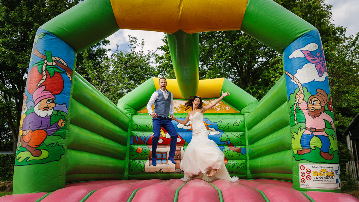 bride groom wedding couple having fun jumping on bouncy castle journalistic documentary reportage photographer photography photo surrey