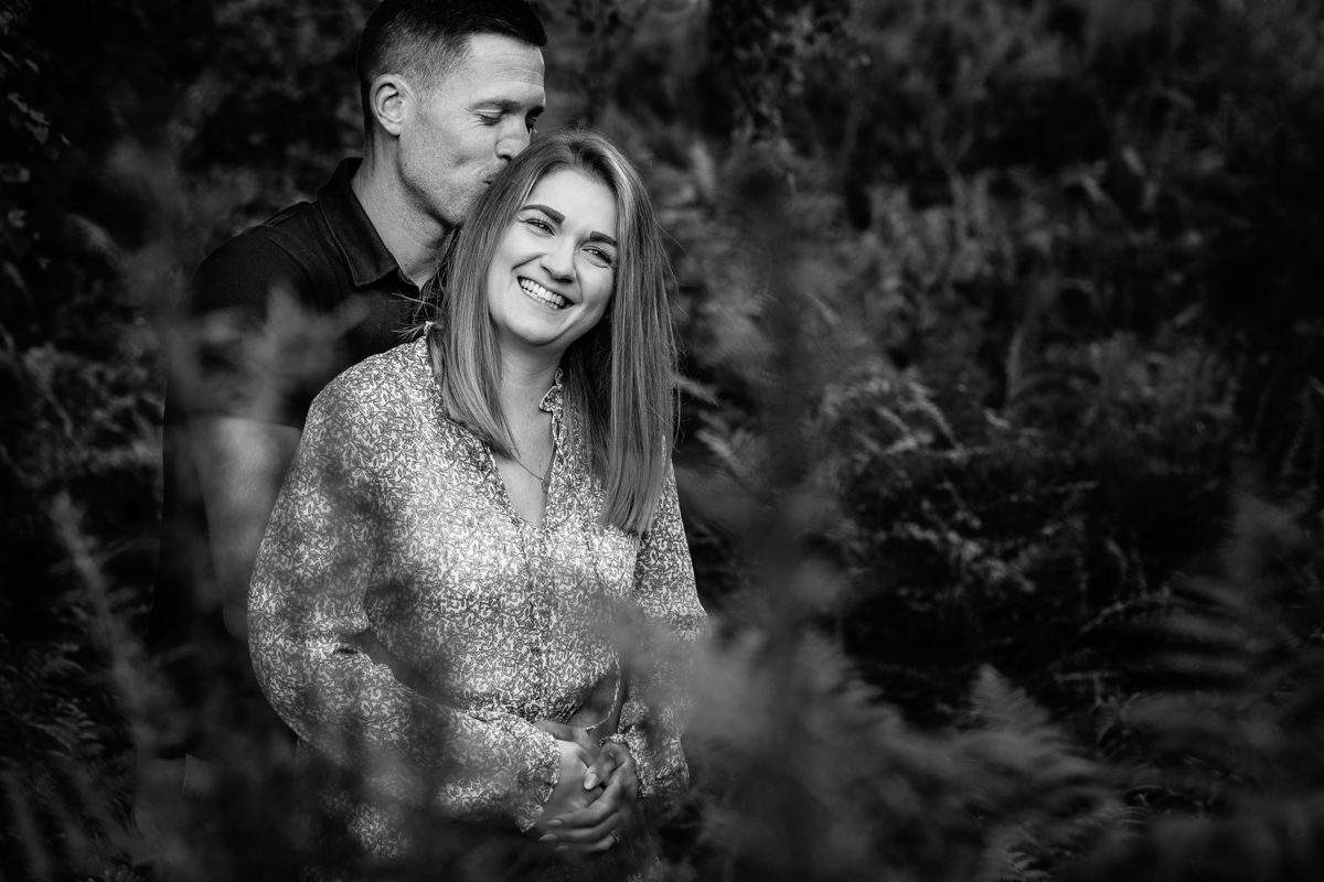 happy smile black-white natural authentic image couple embrace in ferns headily heath surrey hills unposed engagement session outdoor pre-wedding_shoot natural light documentary wedding photographer