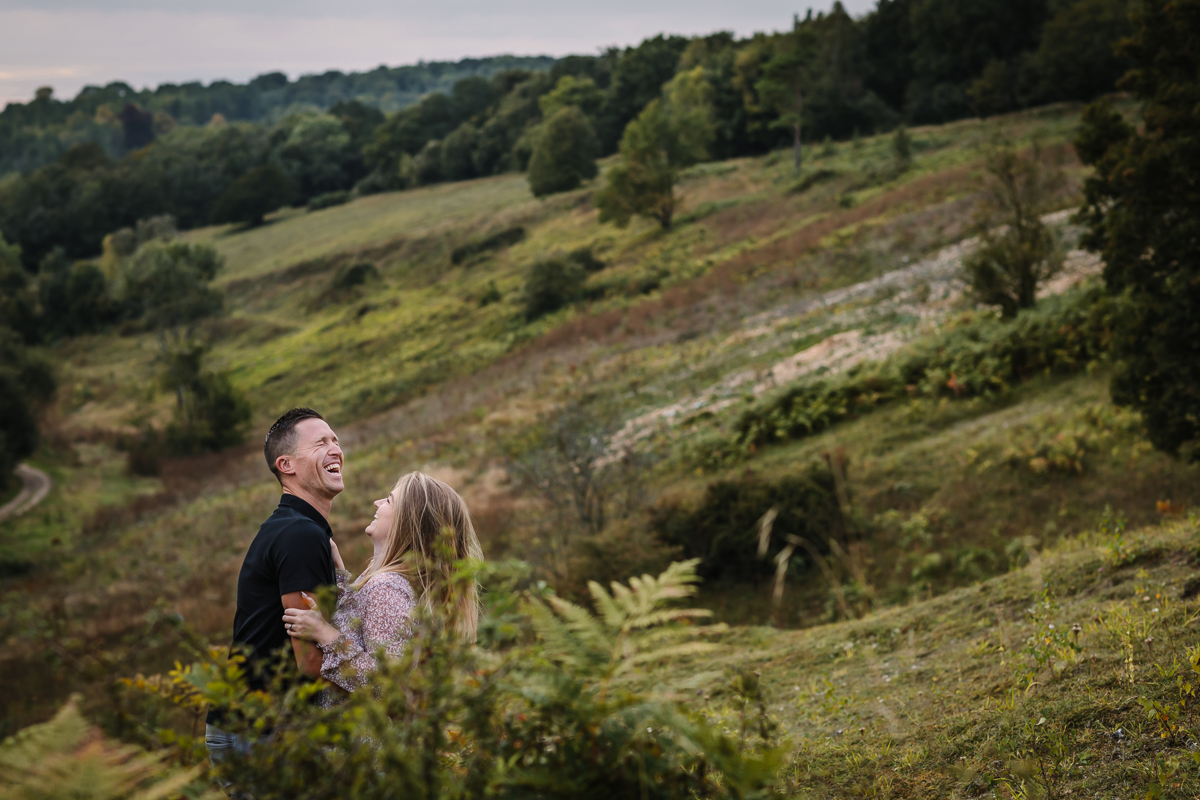 happy smiling natural authentic image couple embrace in ferns headily heath surrey hills unposed engagement session outdoor pre-wedding_shoot natural light documentary wedding photographer