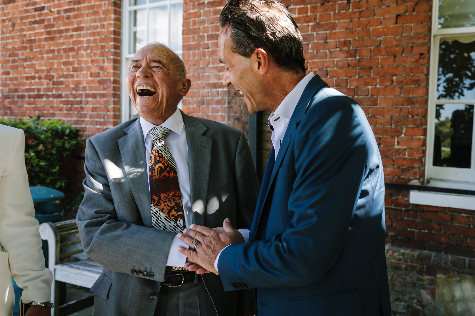 groom and father of the groom emotional happy smiling moment natural authentic documentary wedding photo bride groom couple beaverbrook surrey hills leatherhead register office wedding photographer