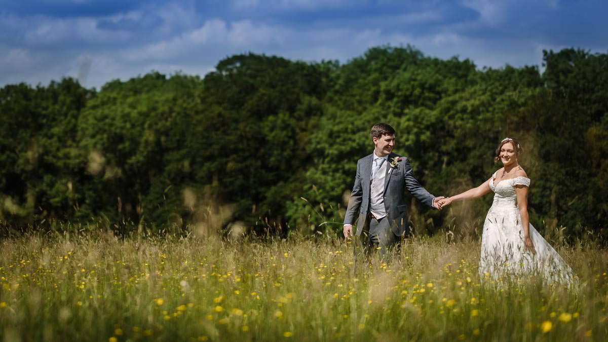bride-groom-walking-flower-field-sunny-day-gildings-barns-wedding-venue-surrey-documentary-photography